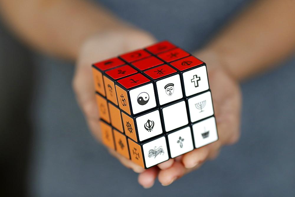 Woman with a Rubik's cube with religious symbols, Interreligious and interfaith dialog concept, Vietnam, Indochina, Southeast Asia, Asia