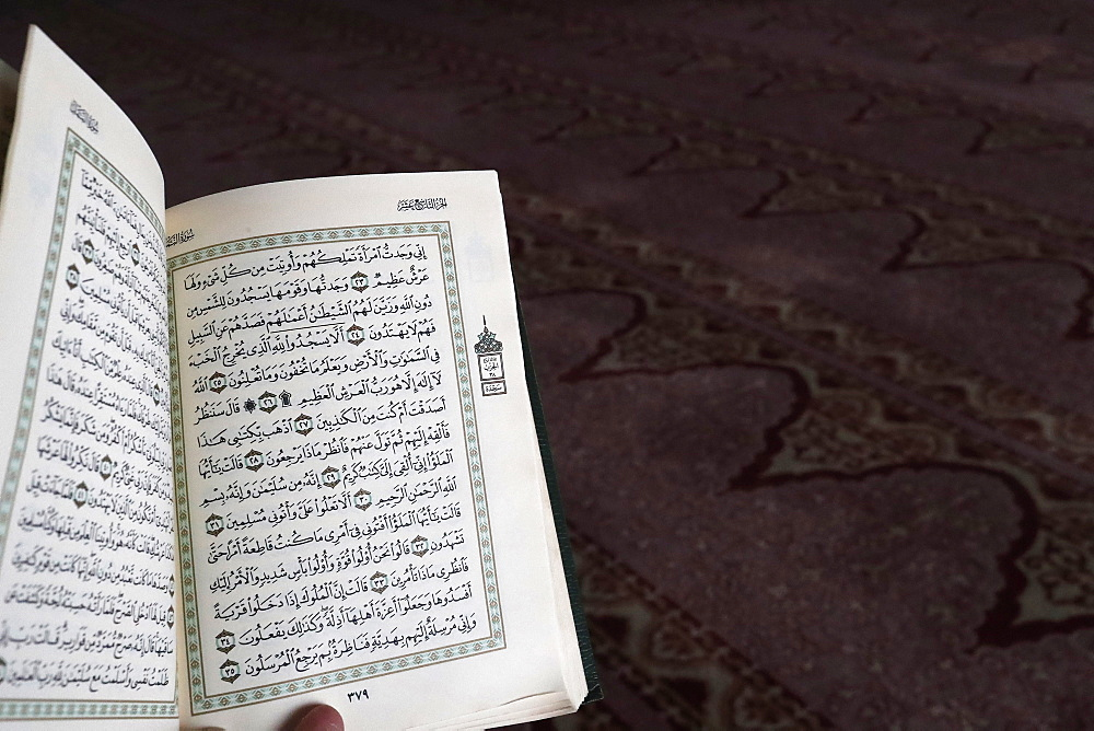 Close up on hand with open Quran, Putra Mosque (Masjid Putra), Putrajaya, Malaysia, Southeast Asia, Asia