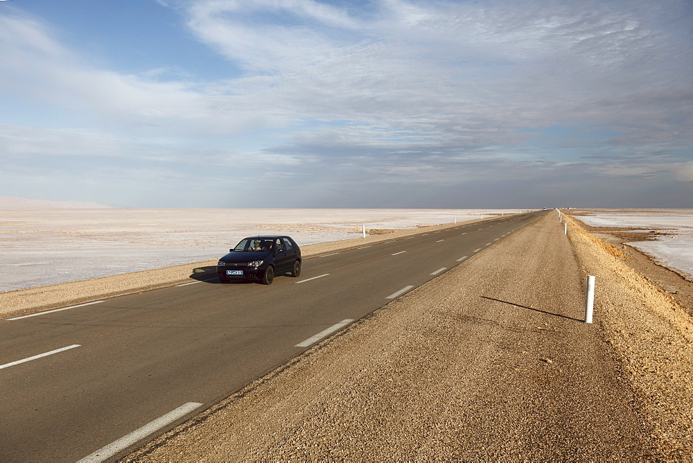 Chott El Jerid, a flat dry salt lake, and automobile on highway between Tozeur and Kebili, Tunisia, North Africa, Africa - 813-169
