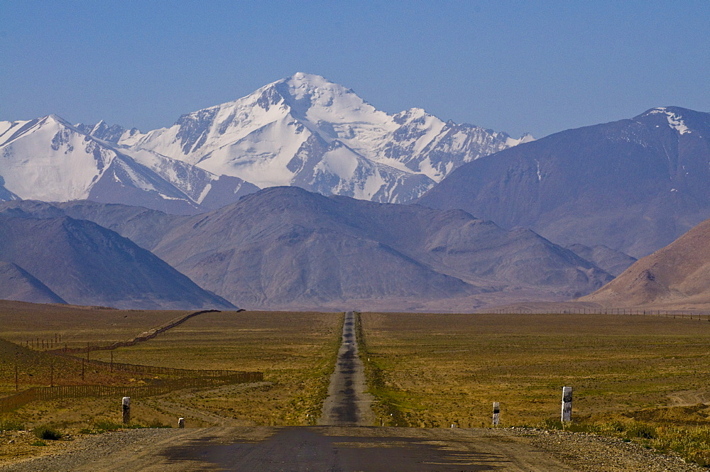 Country road leading to snow covered mountains, Karakul, Tajikistan, Central Asia
