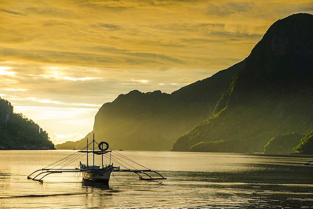 Outrigger at sunset in the bay of El Nido, Bacuit Archipelago, Palawan, Philippines, Southeast Asia, Asia