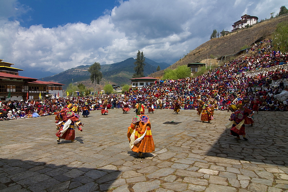 Costumed dancers at religious festival with many visitors, Paro Tsechu, Paro, Bhutan, Asia