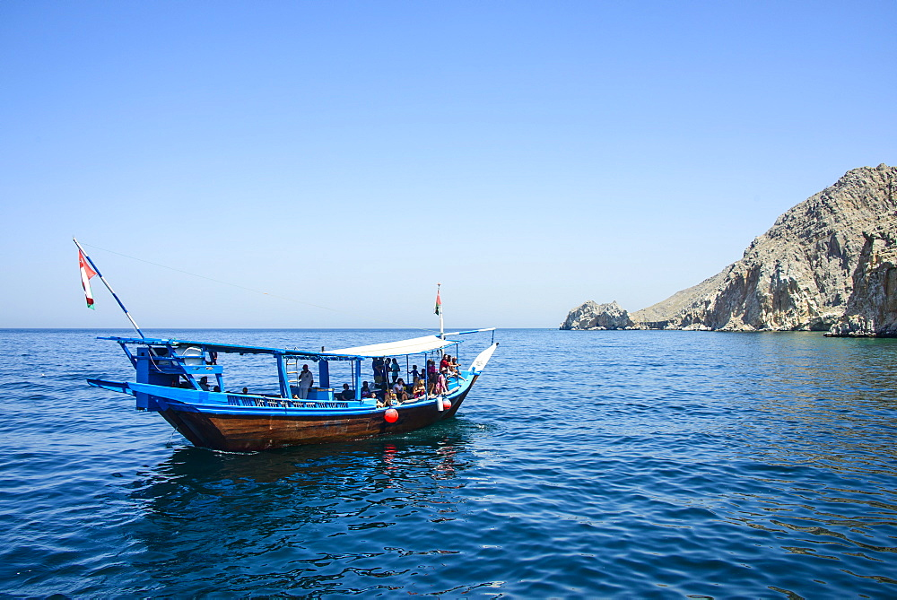 Tourist boat in form of a dhow sailing in the Khor ash-sham fjord, Musandam, Oman, Middle East