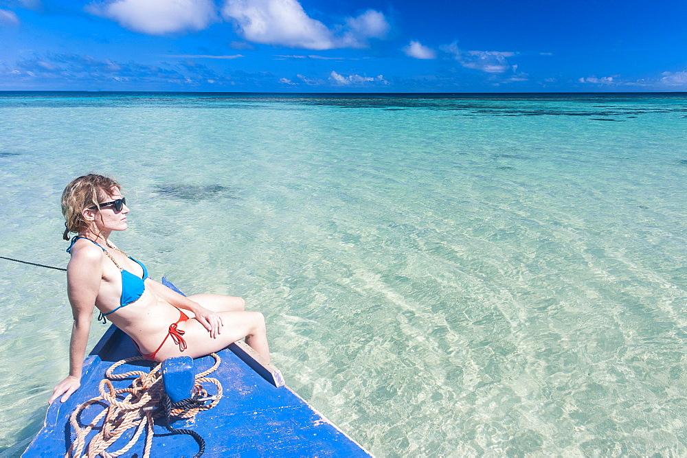 Woman relaxing on little motor boat, Haapai, Haapai Islands, Tonga, South Pacific, Pacific