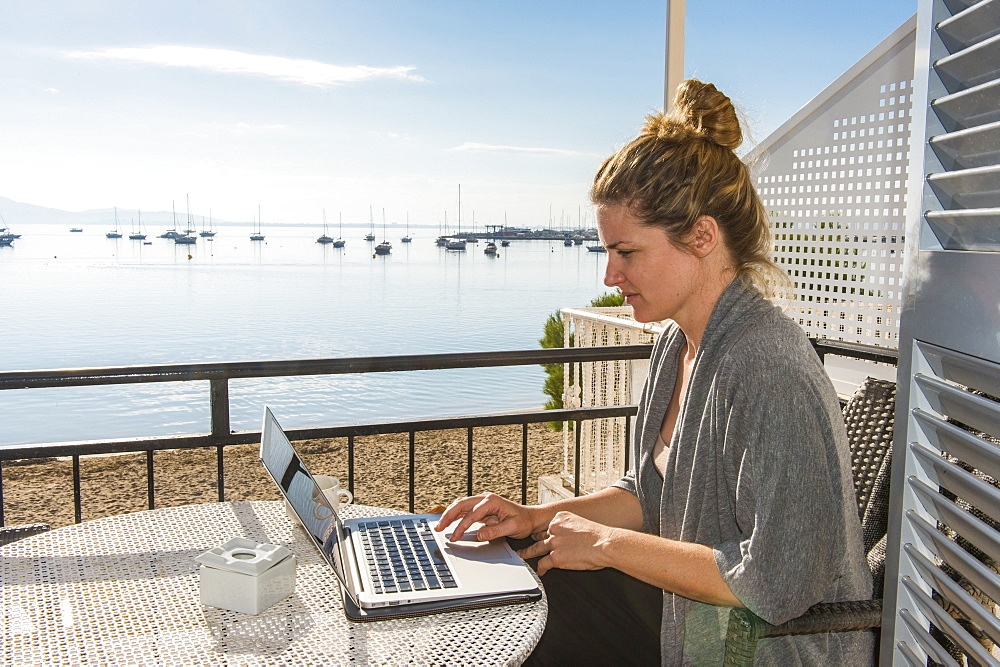 Woman working on her laptop on a balcony overlooking the ocean, Port de Pollenca, Mallorca, Balearic Islands, Spain, Mediterranean, Europe