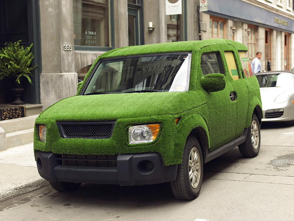 SUV covered in green grass portraying an enviro-friendly automobile, Quebec, Canada, North America - 818-234