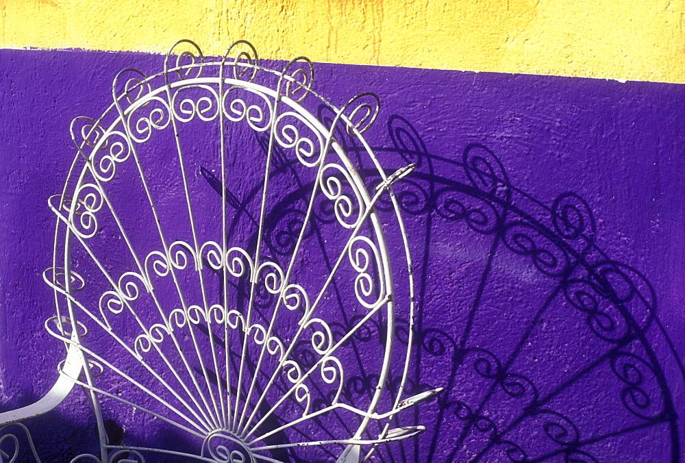 Chair casting a shadow on yellow and purple wall, Playa del Carmen, Quintana Roo, Yucatan, Mexico, North America