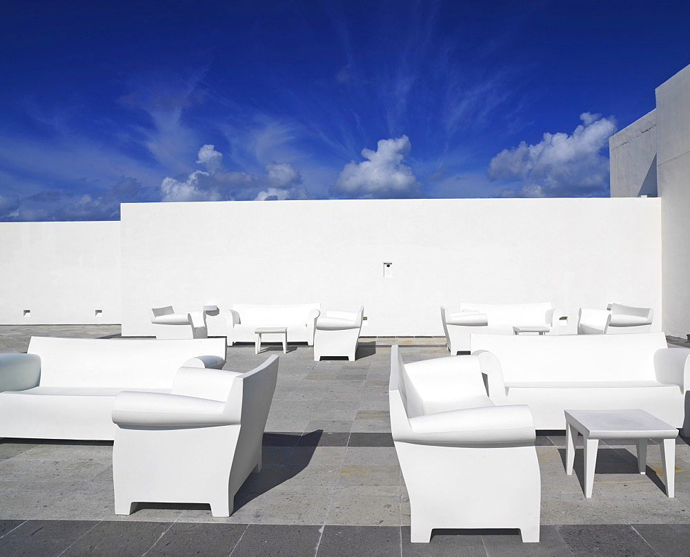 White chairs and white couches against a white wall and blue sky in a surreal setting, Mayan Riviera, Akumal, Yucatan, Quintana Roo, Mexico, North America
