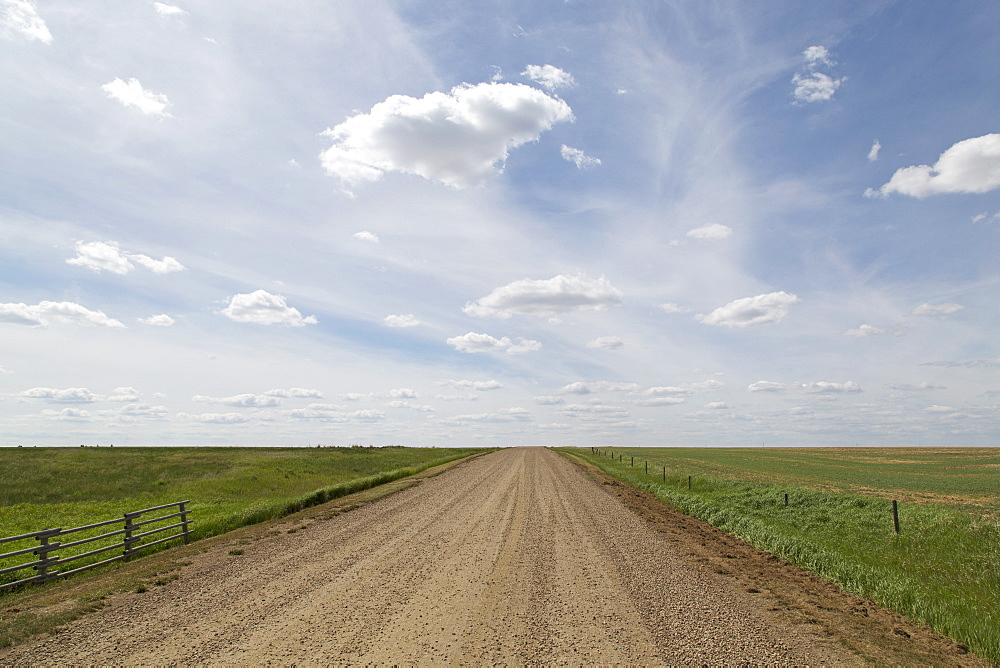 Clouds and blue sky over a dirt track in the Badlands of Alberta, near Drumheller, Alberta, Canada, North America - 826-675