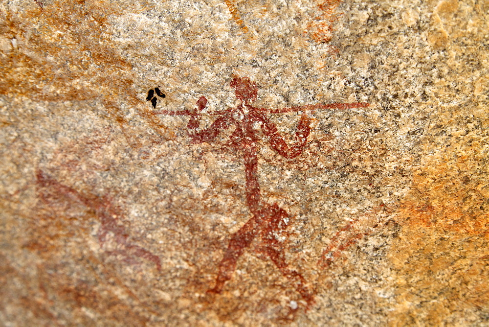 Ancient rock art of painting depicting a human carrying a spear, at Matobo National Park, Zimbabwe, Africa - 826-697