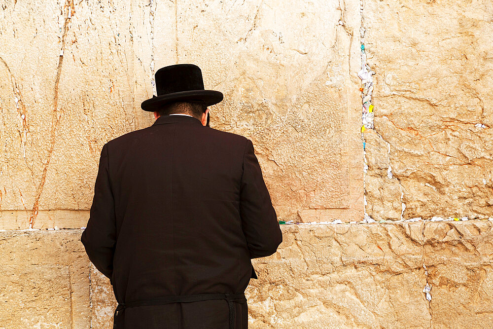 A Jewish man wearing Orthodox clothing prays by the Western Wall (Wailing Wall), Jerusalem, Israel, Middle East