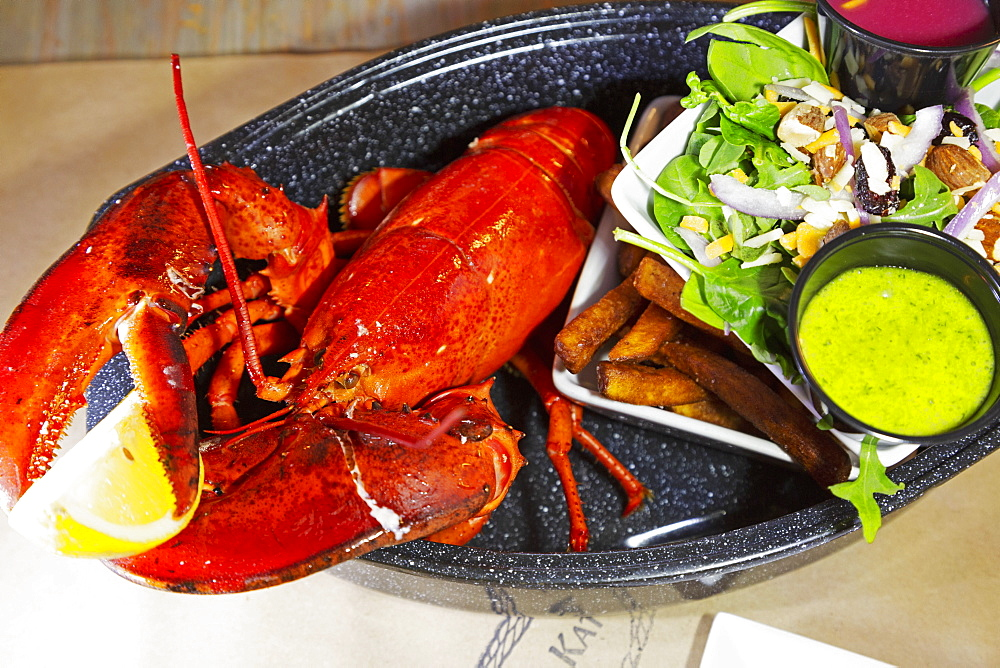 A lobster dinner served with salad, sauces and French fries in Barrington, Nova Scotia, Canada, North America