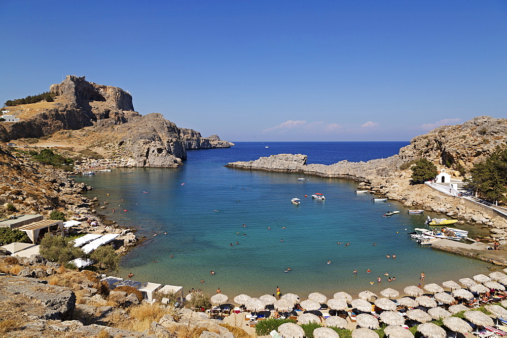The Lindian Acropolis rises over St Paul's Bay, a cove lined by sun shades, on a sunny day in Lindos on Rhodes, Greece