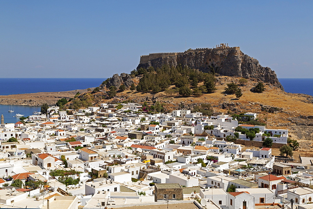 The Lindian Acropolis, site rises over white houses in the fishing village of Lindos on Rhodes, Dodecanese, Greek Islands, Greece, Europe