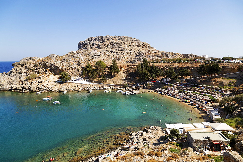 Sun shades line the beach at St Paul's Bay on a sunny day in Lindos on Rhodes, Greece