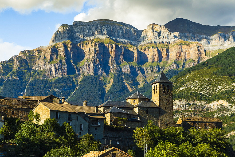 Torla village & church and Mt Mondarruego (Red Mountain) in Ordesa National Park beyond. Torla; Pyrenees; Huesca; Aragon; Spain - 83-13038