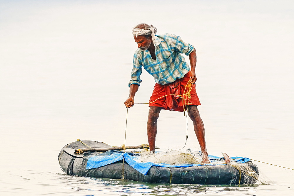 Fisherman retrieving net on small raft offshore of popular Marari Beach; Mararikulam, Alappuzha (Alleppey), Kerala, India