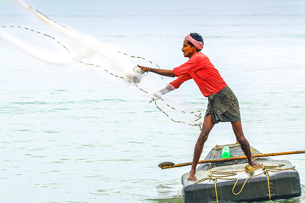 Fisherman casting weighted net on small raft offshore of popular Marari Beach; Mararikulam, Alappuzha (Alleppey), Kerala, India