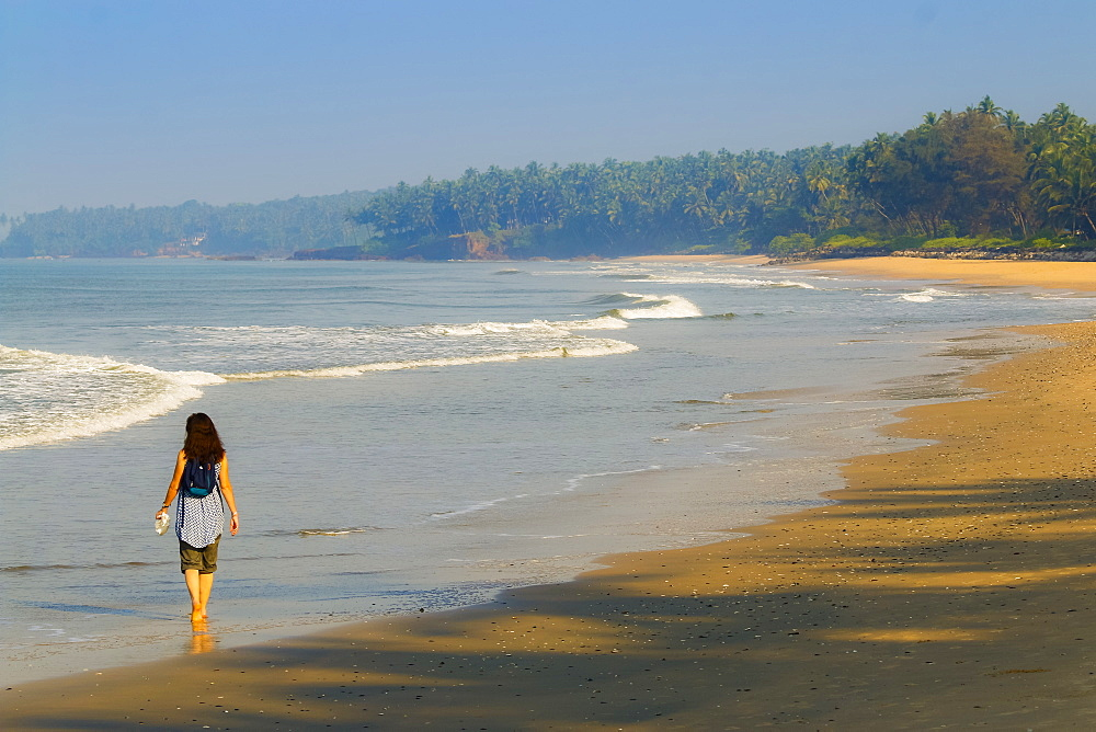 Lone traveller on lovely palm-fringed, Kizhunna Beach, south of Kannur on Kerala's north coast, Kizhunna, Kannur, Kerala, India, Asia