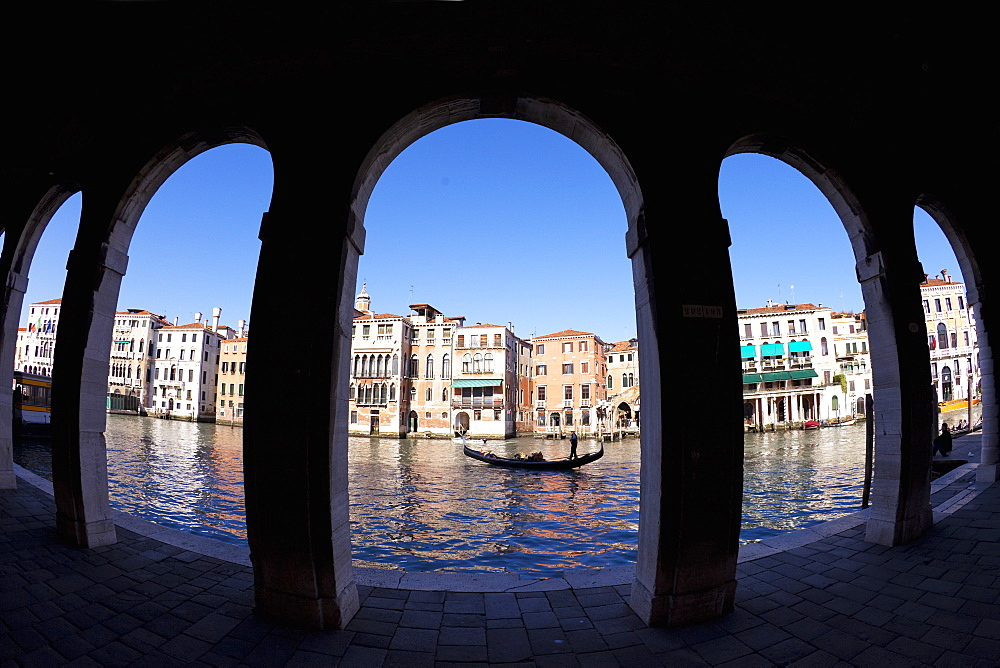 Gondola and gondolier taken through arches of the Rialto Market area, San Polo, Venice, UNESCO World Heritage Site, Veneto, Italy, Europe