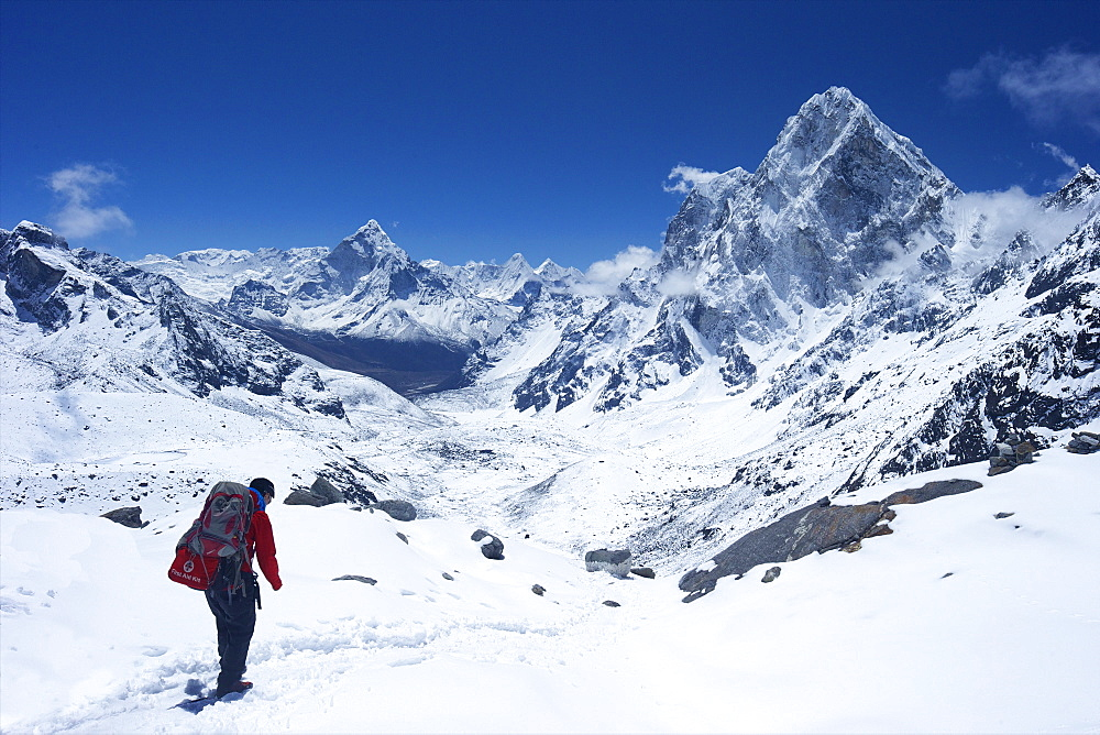 Sherpa guide walking over Cho La Pass with Ama Dablam on left and Arakam Tse on right side, Solukhumbu District, Nepal, Himalayas, Asia