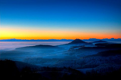 Dawn atmosphere, mist-covered Hegau volcanic range, with only the highest peaks Hohenhewen and Hohenstoffel exposed, Swiss Alps in background, Hegau, Baden-Wuerttemberg, Germany, Europe