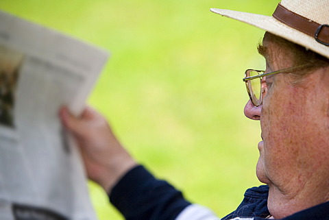 A relaxing senior citizen sitting in the garden reading a newspaper