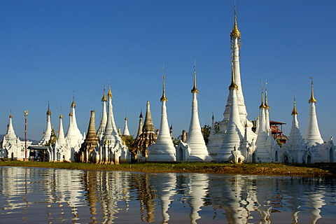 Slim stupas of Aung Min Ga Lar Paya reflect in the water Inle Lake Shan State Burma