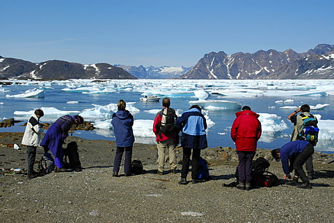 People watch ice pack and icebergs in Ammassalik Fjord near Kulusuk Eastgreenland