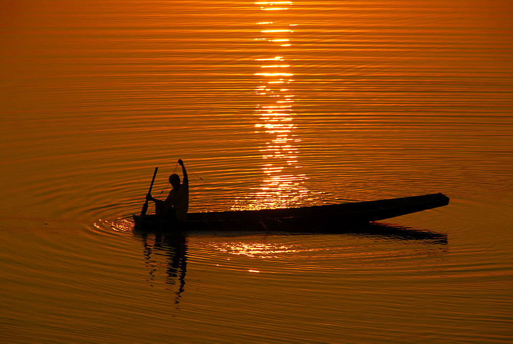 Sundown fisherman is fishing in his fishing boat in the Mekong River Vientiane Laos