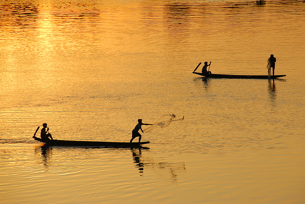 Sunset fishermen in boats throwing nets on the Mekong River Muang Khong Si Phan Don Laos