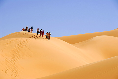Group of tourists descent a sanddune Mandara Libya
