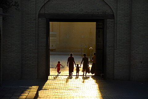 Human silhouettes against sunlight in the Ota Darvoza Gate in the old town Khiva Uzbekistan