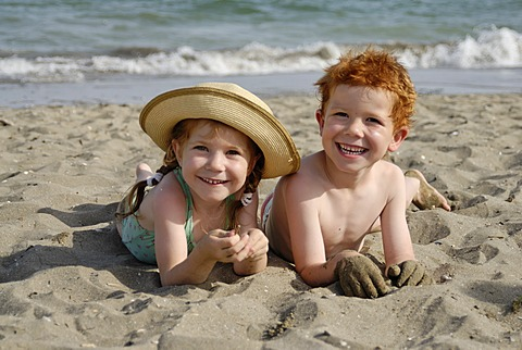 Two children are lying on a sandy beach at the sea