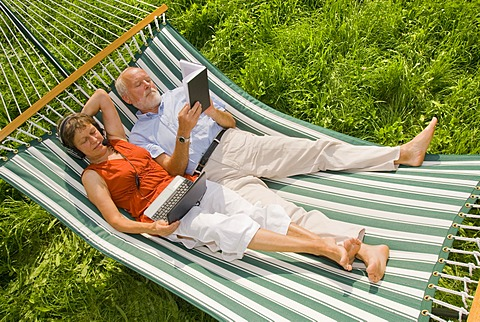 Senior citizen couple lying in a hammock, woman wearing a headset looking at a netbook or laptop, man reading a book