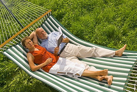 Senior citizen couple lying in a hammock, woman listening to music, man reading a book