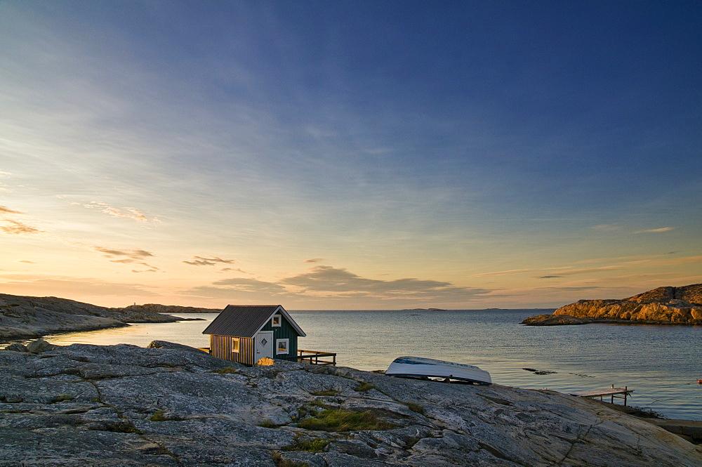 Wooden hut on rocky coast with sunset, Smoegen, Bohuslaen, Sweden, Scandinavia, Europe