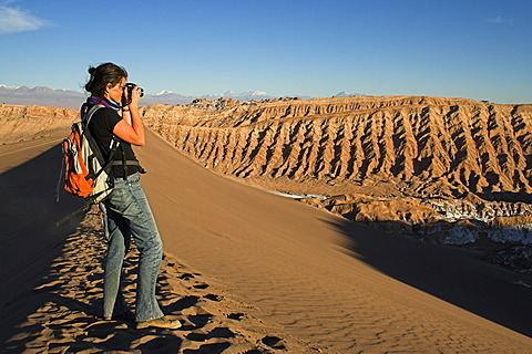 Woman with a camera on a sand dune in the Moon Valley (Valle de la luna), Atacama desert, northern Chile, South America