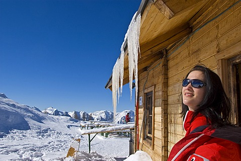 Young woman basking in the sun, sitting outside a cabin, icicles overhead