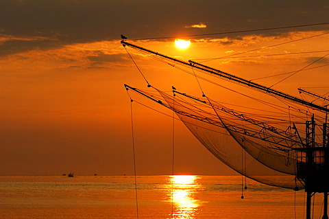 Fishing nets hanging up to dry above the sea at sunrise, Veneto, Italy - 832-376032
