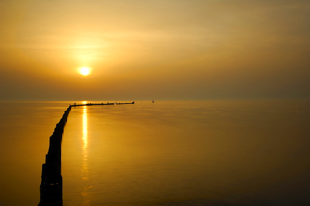 Calm sea with breakwater at sunrise, the rising sun is reflected in the water, Veneto, Italy