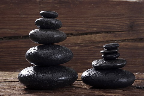 Hot stone massage stones on a wooden beam