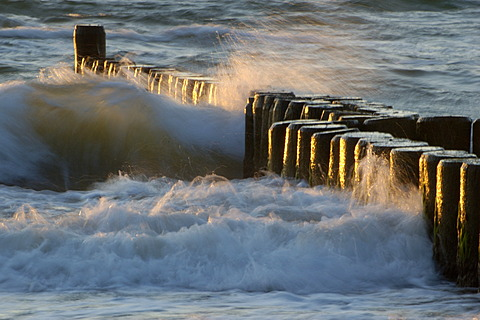 Waves breaking at a groyne at dusk Baltic Sea Germany
