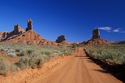 Dirtroad between sandstone buttes in Valley Of The Gods Utah USA