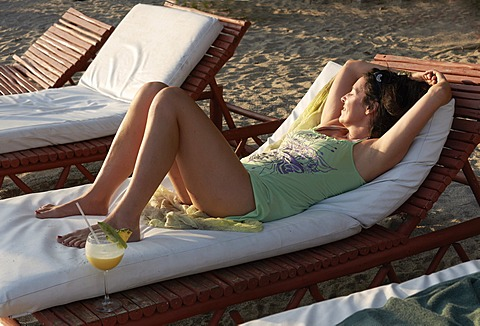 Woman, 45 years, in a beach outfit, relaxing on a sun lounger with a piña colada cocktail, Playa Samara, Nicoya Peninsula, Costa Rica, Central America