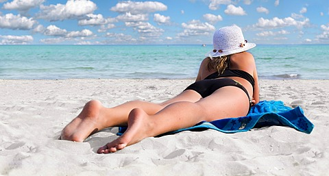 Girl with hat on a white sandy beach with turquoise sea lying on a blue towel