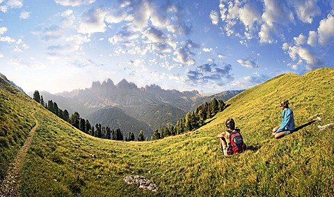 Hikers relaxing in a meadow enjoying the view of the Geisler group, Aferer Geisler mountains, Villnoesstal valley, province of Bolzano-Bozen, Italy, Europe