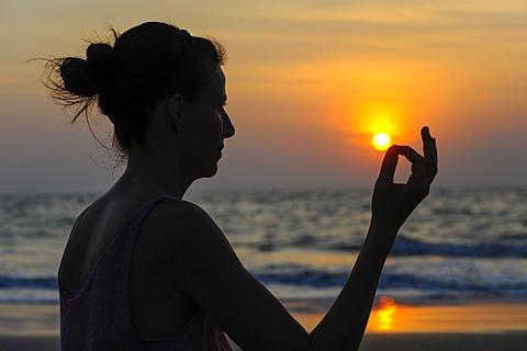 Woman meditating on a beach at sunset, Kerala, India