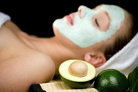 Young woman with a facial avocado mask