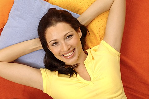 Young woman relaxing on pillows